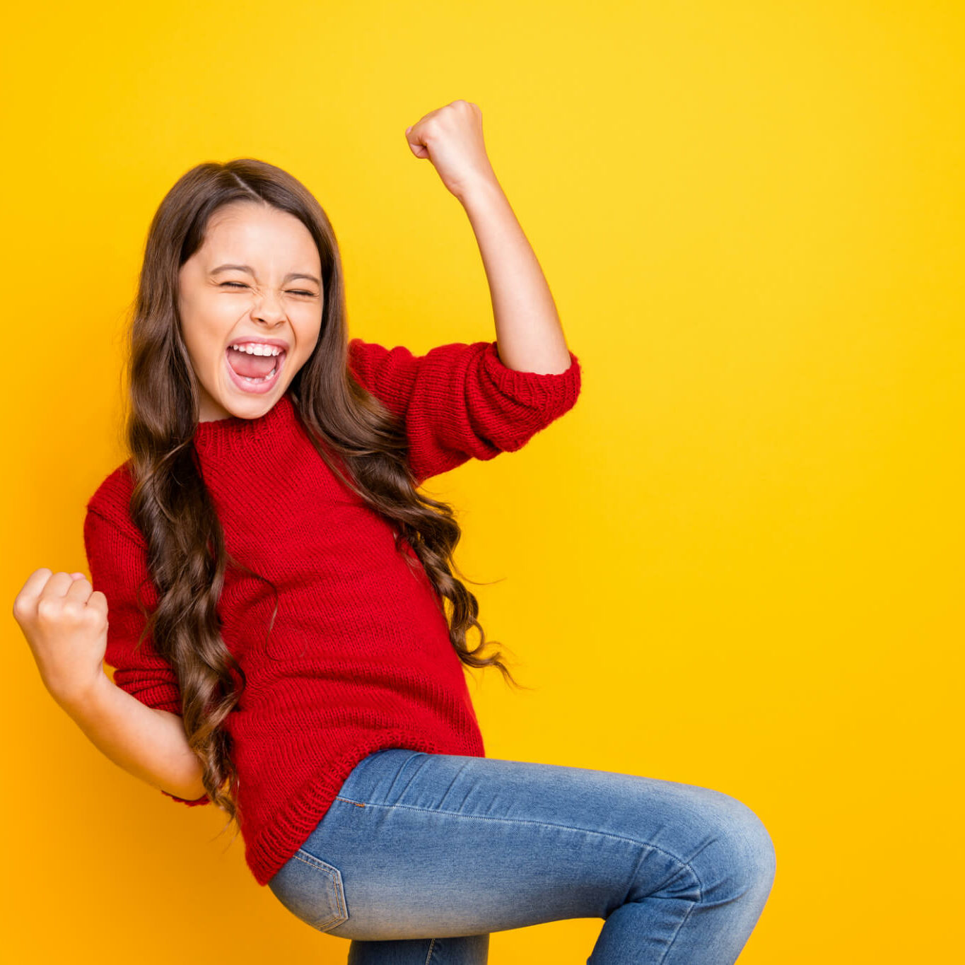 Portrait of delighted positive lucky cheerful kid feel crazy funky rejoice raise, fists scream yeah celebrate achievements aims wear style sweater denim jeans isolated over yellow color background